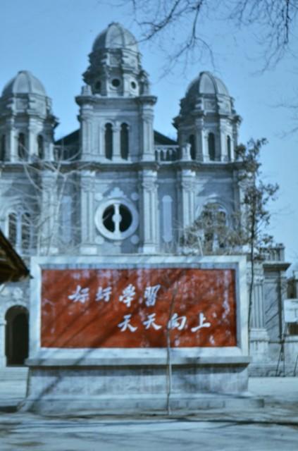 Плакат с комунистически лозунги пред Католическата катедрала в Пекин