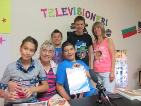 Малките телевизионери, заедно с ръководителката си г-жа Мария Илиева и с г-жа Калина Томова, показват с гордост част от своите отличия и награди.