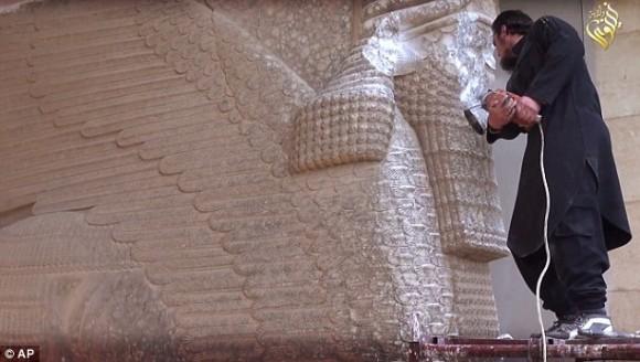 Войнстващия използва инструмент за власт, за да се унищожи един крилат бик асирийската защитно божество в Музея Ninevah в Мосул, Ирак. Статуята датира от 9 век преди Христаdailymail.co.uk